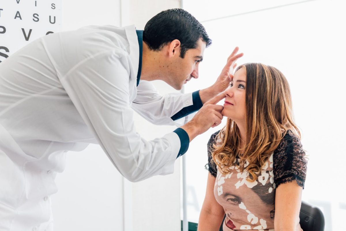 Eye doctor inspecting a womans eyes
