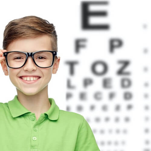 Child in front of eye exam smiling